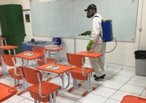 Especialista sanitizando sala de aula